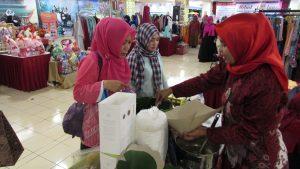 Aminah saat melayani pembeli makanan Semanggi Suroboyo di stan acara Bedah Buku Otot Kawat Balung Wesi