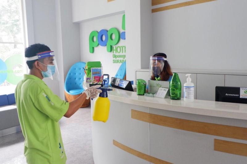 Salah satu karyawan Pop! Hotel membersihkan meja receptionist Pop! Hotel dengan disinfektan